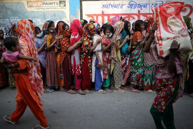 Women stand in a queue to receive relief supplies provided by local community amid the coronavirus disease (COVID-19) outbreak in Dhaka, Bangladesh, April 1, 2020. (Photo by Mohammad Ponir Hossain/Reuters)