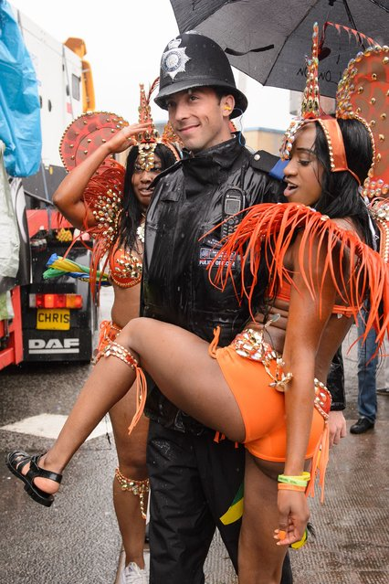 A performer dances with a police officer during the parade on the second day of the Notting Hill Carnival in west London on August 25, 2014. Heavy rain continued throughout the day, dampening many feathered costumes and performers. The Notting Hill Carnival honours London's Afro-Caribbean culture in an area which was home to thousands of immigrants to Britain from the Caribbean in the 1950s onwards. (Photo by Leon Neal/AFP Photo)