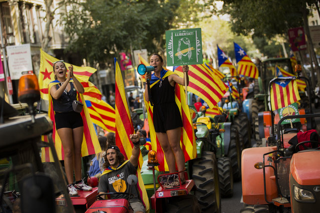 People with the estelada, or independence flags, shout slogans on top of parked tractors during a protest by farmers in Barcelona, Friday, September 29, 2017. (Photo by Francisco Seco/AP Photo)