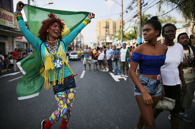 A fan waves a Brazilian flag before the arrival of the Olympic torch ahead of the Rio 2016 Olympic Games on August 2, 2016 in Sao Goncalo, Rio de Janeiro state, Brazil. The torch will arrive in the city of Rio tomorrow and the Games commence on August 5. (Photo by Mario Tama/Getty Images)