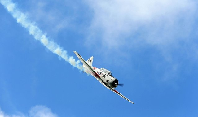 A pilot performs aerobatics in a vintage Harvard aircraft during an airshow commemorating the completion of the the rebuild of Havilland Mosquito KA 114, on September 29, 2012 in Ardmore, New Zealand. The plane was restored by Warbird Restorations at Ardmore Aerodrome and is the only flying Mosquito in the world.  (Photo by Simon Watts)
