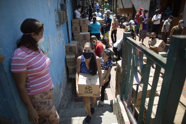 A woman wearing face mask against the spread of the new coronavirus, carries a box of basic food staples such as pasta, sugar and flour, provided by a government food assistance program, in Caracas' slum of Petare, Venezuela, Thursday, April 30, 2020. The program known as Local Committees of Supply and Production, CLAP, provides highly subsidized food for which recipients pay less than the equivalent of $0.50 per box. (Photo by Ariana Cubillos/AP Photo)