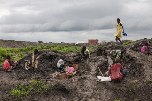 Children collect dirt to reinforce their shelters during the rainy season at the Protection of Civilians (POC) site at the United Nations Mission in South Sudan (UNMISS) compound in Malakal, South Sudan on Wednesday, July 13, 2016. (Photo by Jane Hahn/The Washington Post)
