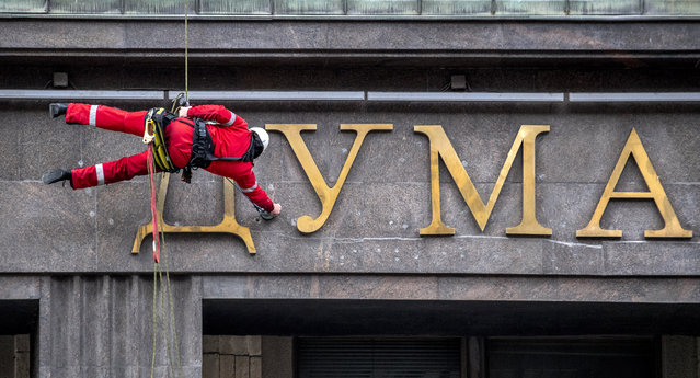 A worker cleans letters on the wall of the Russian State Duma (the lower house of the parliament) in central Moscow on May 17, 2020, during a strict lockdown in Russia to stop the spread of the novel coronavirus COVID-19. (Photo by Yuri Kadobnov/AFP Photo)