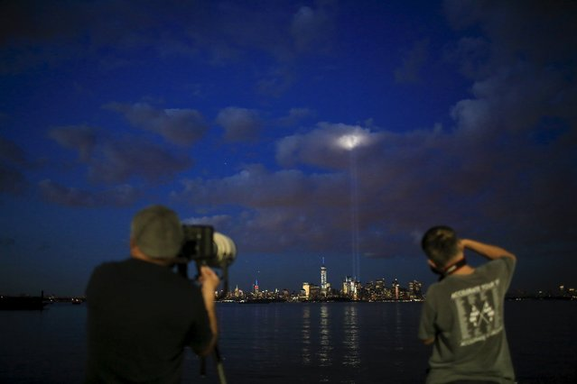 People take pictures of the Tribute in Light as it is illuminated next to the One World Trade Center during events marking the 14th anniversary of the 9/11 attacks on the World Trade Center in New York September 11, 2015. (Photo by Eduardo Munoz/Reuters)