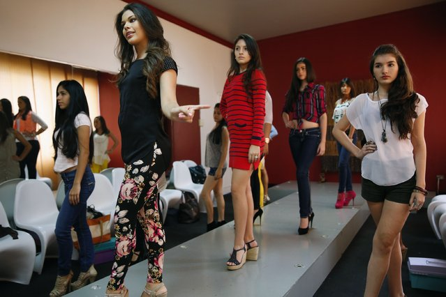 Girls practice on the runway during a class at a modelling academy in Caracas September 20, 2014. (Photo by Carlos Garcia Rawlins/Reuters)