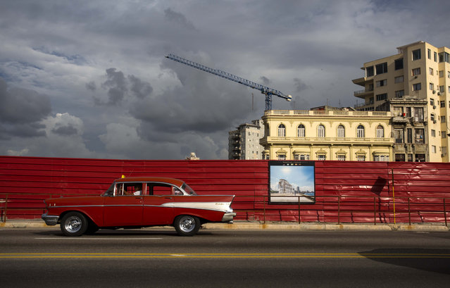 In this June 9, 2016 photo, a classic American car drives past an empty lot where a hotel is projected to be built along the Malecon sea wall in Havana, Cuba. A year and a half into normalization with the U.S., Cuba faces either an exciting new era of foreign investment or another in a string of false starts. (Photo by Desmond Boylan/AP Photo)