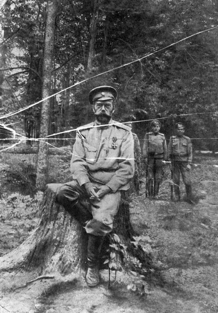 In this photo taken in spring-summer of 1917, provided by Russian State Documentary Film and Photo Archive, Russia's deposed Czar  Nicholas II, sits on a tree stump, three of the soldiers that held him captive standing in the background in Tsarskoe Selo, the residence of the Russian czar, outside St. Petersburg, Russia. Nicholas, his wife Alexandra and their five children were executed by Bolsheviks in 1918 . The 1917 Bolshevik Revolution was long before the digital revolution allowed anyone to instantly document events. But the clumsy cameras of the time still caught some images that capture the period's drama. (Photo by Russian State Documentary Film and Photo Archive via AP Photo)