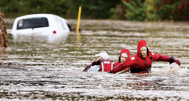 Alton, Ill., Fire Department Batallion Chief Brad Sweetman, right, and Alton Capt. Matt Fischer, center, help pull an unidentified man to safety Thursday morning, October 2, 2014, after the man's vehicle was overcome by a flash flood in Jersey County, near Alton, Ill. The man, who had been trapped with his vehicle since about 4 a.m., was exhausted from the ordeal but uninjured.  (Photo by John Badman/AP Photo/The Telegraph)