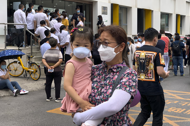A woman and a child wearing protective face masks to help curb the spread of the new coronavirus walk by people lining up outside a health center to get the nucleic acid test in Beijing, Monday, June 15, 2020. China's capital was bracing Monday for a resurgence of the coronavirus after more than 100 new cases were reported in recent days in a city that hadn't seen a case of local transmission in more than a month. (Photo by Andy Wong/AP Photo)