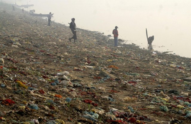 Rag pickers search for recyclable materials from the polluted banks of the Yamuna river in Allahabad December 14, 2009. (Photo by Jitendra Prakash/Reuters)