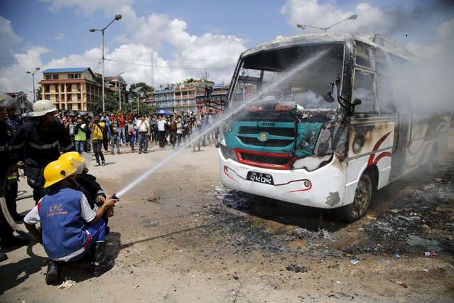 Firefighters try to douse fire set by unidentified protesters on a passenger bus during the nationwide strike, called by the opposition parties against the proposed constitution, in Kathmandu, Nepal September 20, 2015. (Photo by Navesh Chitrakar/Reuters)