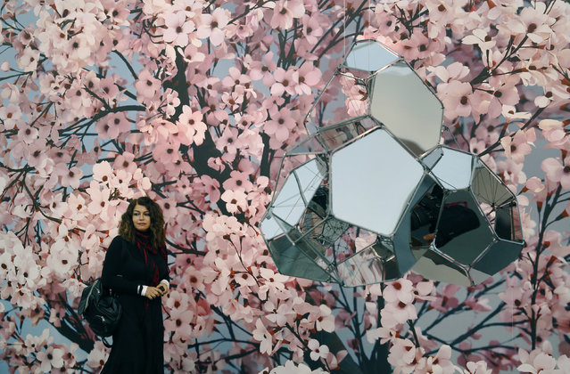"""A visitor passes artworks """"Hanami"""" by Thomas Demand and """"NGC 5892"""" (R) by artist Tomas Saraceno at the Frieze Art Fair in London, October 14, 2014. (Photo by Luke MacGregor/Reuters)"""