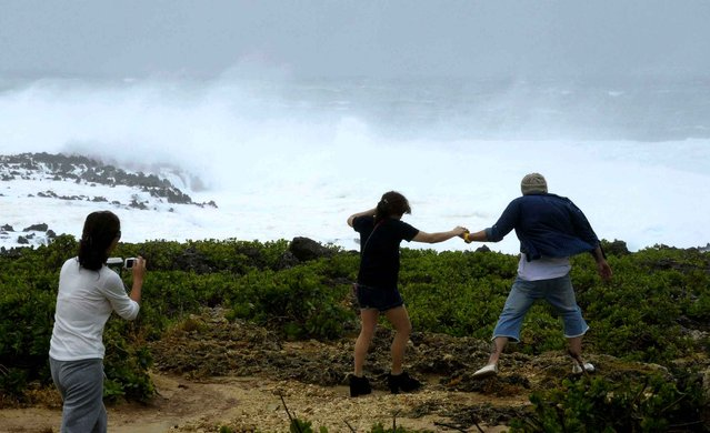 People visit a cape to watch rough sea in Yomitan Village, Japan's southern island of Okinawa Sunday, October 12, 2014. A powerful typhoon poured heavy rains over Okinawa and was aiming at the next island of Kyushu on Sunday, becoming the second severe storm to hit in a week. (Photo by AP Photo/Kyodo News)