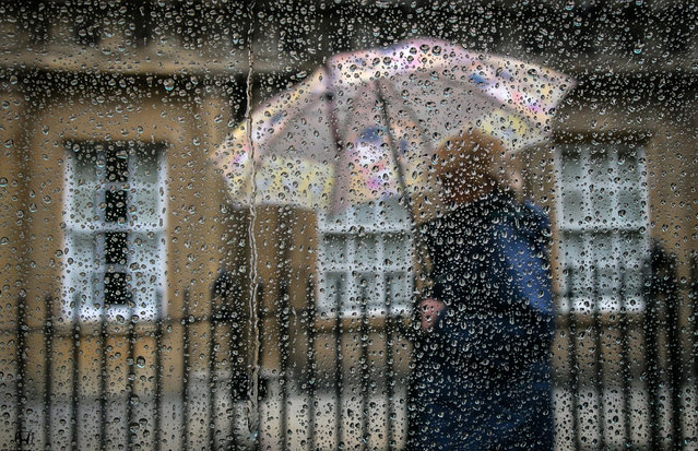 A woman passes a window covered in rain drops on October 6, 2014 in Bath, England. After one of the warmest and driest September months in recent years, the weather for October has turned much more autumnal, with a period of unsettled weather forecasted bringing much more wet and windy conditions to the UK. (Photo by Matt Cardy/Getty Images)
