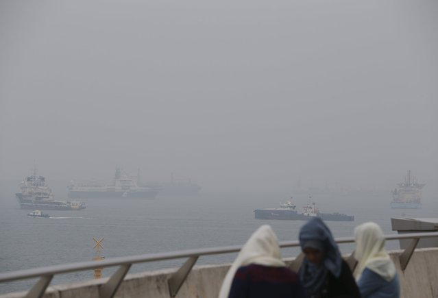 Women watch vessels pass an anchorage area shrouded by haze in the southern coast of Singapore September 29, 2015. (Photo by Edgar Su/Reuters)