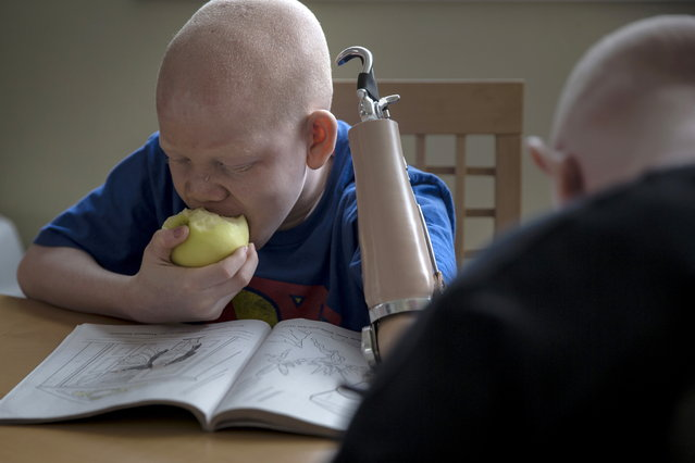 12-year-old Mwigulu Matonage from Tanzania eats an apple as he does homework. (Photo by Carlo Allegri/Reuters)