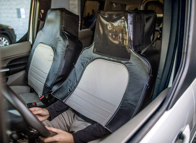"""The Ford and Virginia Tech research simulated a self-driving vehicle using a """"seat suit"""" to conceal the human driver. This was done to explore pedestrian reaction to external lighting signals that indicate when the vehicle is driving, yielding or accelerating from a stop in Arlington, Virginia, in this handout photo obtained by Reuters September 13, 2017. (Photo by Reuters/Ford Motor Company)"""