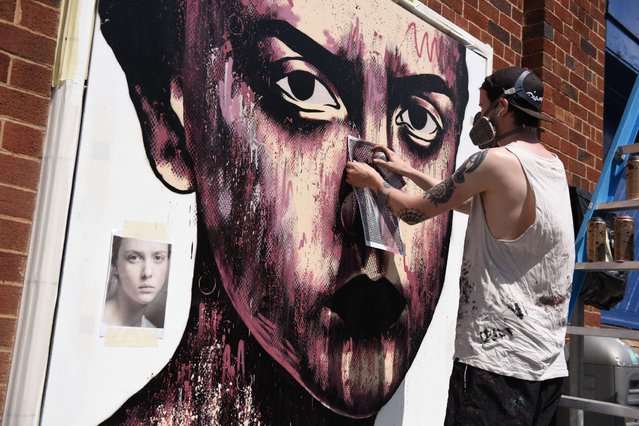 "Street artist Will Bentham, known as ""Lowdown"", creates an artwork as he takes part in the ""Sand Sea & Spray"" Urban Art Festival in Blackpool, north west England on July 11, 2015. (Photo by Oli Scarff/AFP Photo)"