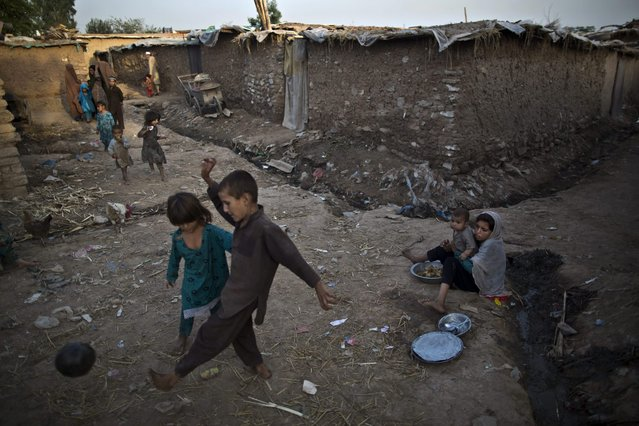 Afghan refugee children, play with a ball, while a girl holding her brother, sits on the ground of an alley selling food, at a poor neighborhood on the outskirts of Islamabad, Pakistan, Sunday, September 28, 2014. (Photo by Muhammed Muheisen/AP Photo)