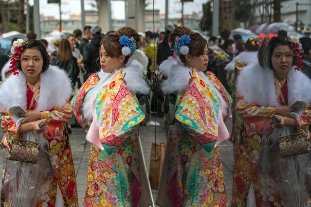 Women wearing kimonos are reflected in glass as they relax after attending a Coming of Age ceremony on January 8, 2018 in Yokohama, Japan. (Photo by Carl Court/Getty Images)