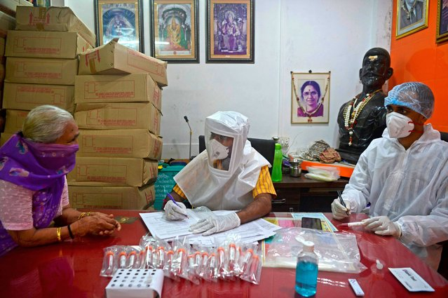 Health workers wearing Personal Protective Equipment (PPE) gear take details of a resident at a COVID-19 coronavirus screening camp in Mumbai on August 17, 2020. India's death toll from the coronavirus hit 50,000 on August 17, with more than 900 new fatalities reported in 24 hours, health ministry data showed. (Photo by Indranil Mukherjee/AFP Photo)