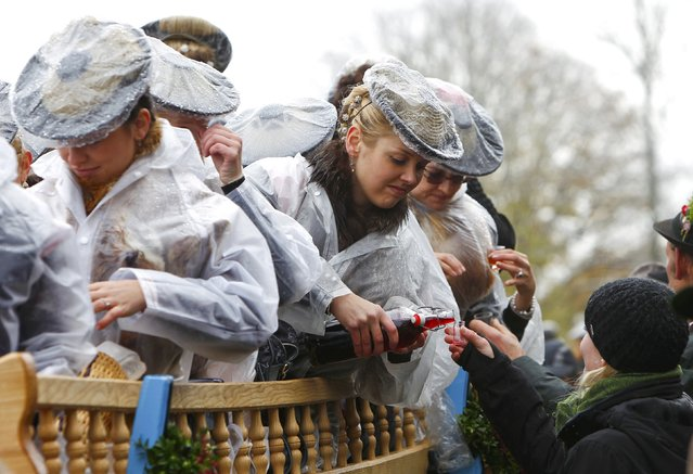 Farmers' wives dressed in traditional Bavarian costumes offer Schnapps, a strong alcoholic beverage, to people during the Leonhard procession in Bad Toelz November 6, 2014. (Photo by Michaela Rehle/Reuters)