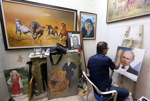Iraqi artist Mohammed Karim Nihaya touches up a painting of Russian President Vladimir Putin in his studio in the Karada district of Baghdad on October 7, 2015. Putins popularity has soared in Iraq since Russia joined the fray in Syria with an aerial campaign and dispatched intelligence officials to Baghdad, in what some Shiite officials see as remedy to the perceived lack of results obtained by the US-led coalition in the fight against the Islamic State group. (Photo by Sabah Arar/AFP Photo)