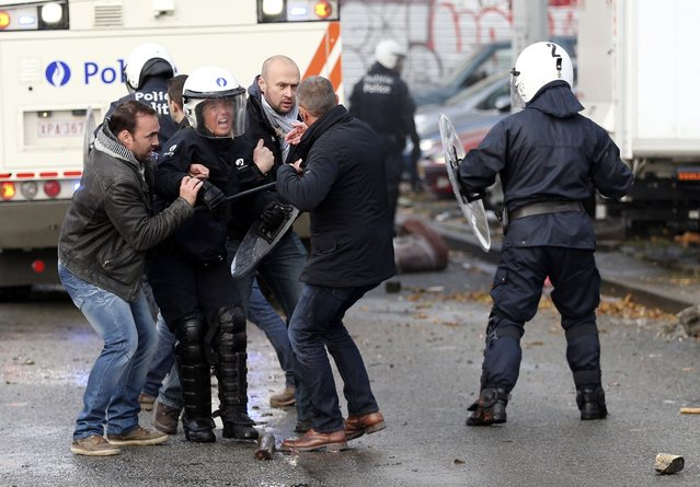 A riot police officer is helped by plainclothes colleagues during a confrontation with demonstrators in central Brussels November 6, 2014. Around 100,000 Belgians marched through central Brussels on Thursday in protest at the new government's proposed reforms and cost-cutting measures, the first in a series of demonstrations and strikes planned over coming weeks. (Photo by Francois Lenoir/Reuters)