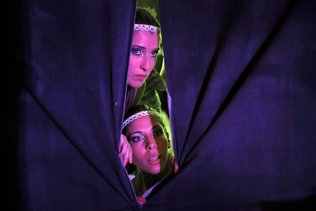 In this photo taken late Friday, September 16, 2016, Argentina's doubles team Ana Laura Ruzicka, bottom and Ana Sofia Bigliardo watch from backstage performances in the doubles finals of the World Pole Dance Sport Championship 2016 in Bucharest, Romania. (Photo by Vadim Ghirda/AP Photo)