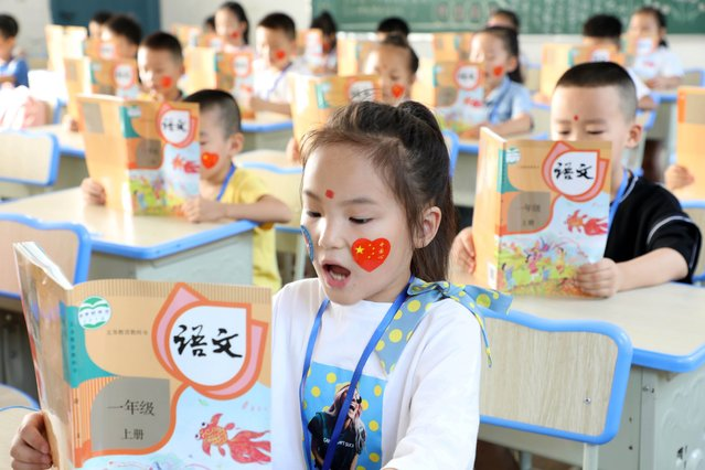 First graders read the lesson on the first day of a new semester on August 31, 2020 in Jiujiang, Jiangxi Province of China. (Photo by Hu Guolin/VCG via Getty Images)