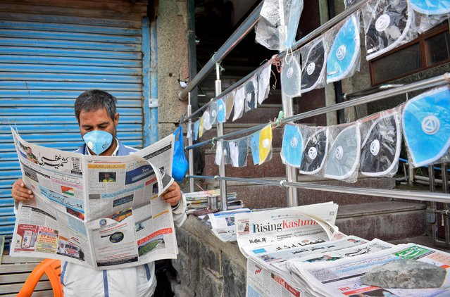 A vendor wearing a protective face mask reads a newspaper at his stall as he sells face masks and newspapers amidst the coronavirus disease (COVID-19) outbreak in Srinagar, September 7, 2020. (Photo by Sanna Irshad Mattoo/Reuters)