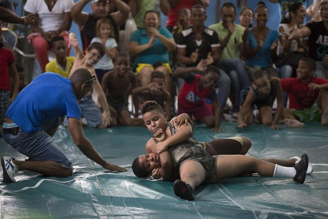 Children fight during a local wrestling tournament in Havana, November 15, 2014. (Photo by Alexandre Meneghini/Reuters)