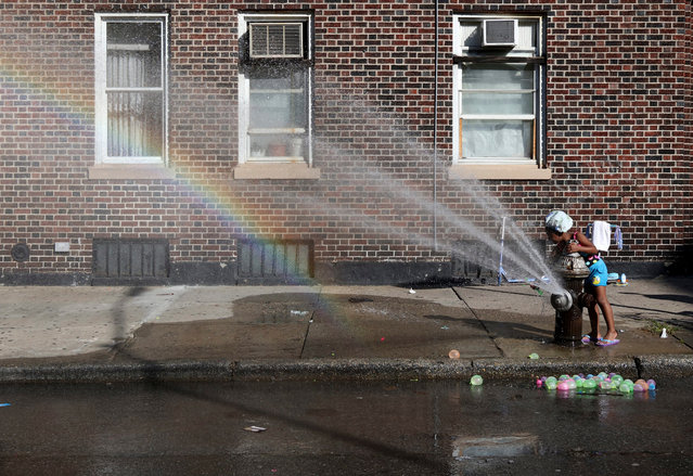 Jenally Canario, five, plays in an open fire hydrant in the Williamsburg section of Brooklyn, New York, USA, 15 August 2016. Temperatures have been in the 90's Fahrenheit (32-degree Celsius) for five consecutive days. (Photo by Andrew Gombert/EPA)