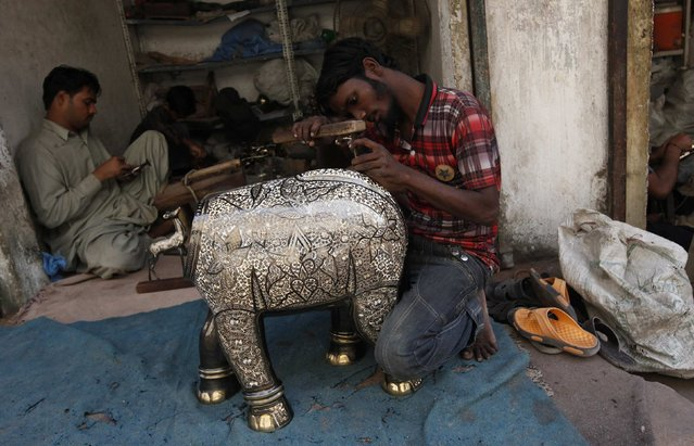 An artisan carves patterns on a brass elephant sculpture at a handicraft workshop along a street in Karachi November 18, 2014. (Photo by Akhtar Soomro/Reuters)