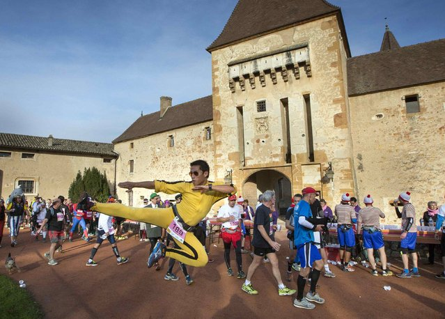 Costumed competitors run during the Marathon International du Beaujolais race at the castle of Pizay, November 22, 2014. (Photo by Robert Pratta/Reuters)