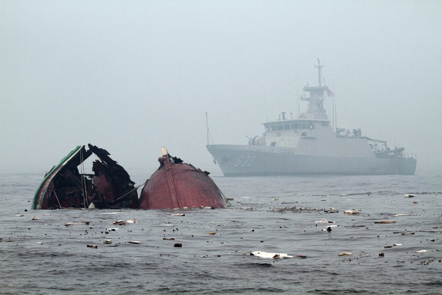 An Indonesian Navy ship patrol as a fishing vessels from Vietnam caught fishing illegally in Indonesian sea start to sink after it were blown up by the Navy, on the water of Pontianak, West Kalimantan province, Indonesia, 19 October 2015. According to media reports, Indonesia has sunk foreign boats across the country, as part of an ongoing push to stop illegal fishing in its waters. (Photo by Yohanes Kurnia Irawan/EPA)