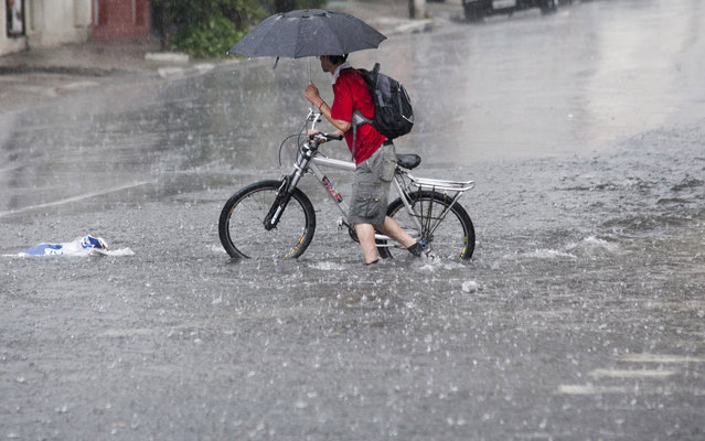 Cyclist on the street, flooded in the district of the Ipiranga, in the Southern District of Sao Paulo, March 8, 2013. (Foto by Edson Lopes Jr./Folhapress)