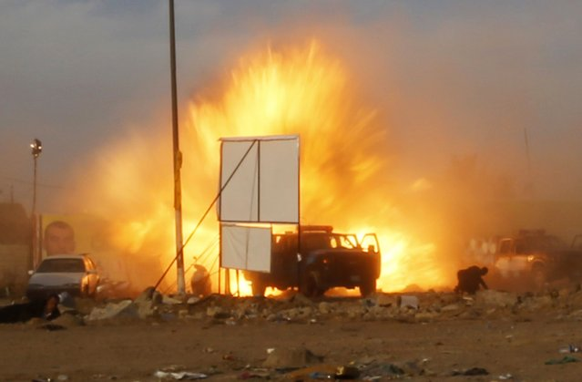 An explosion is seen during a car bomb attack at a rally by militant group, Asaib Ahl Haq (League of the Righteous), to introduce its candidates for elections at a soccer stadium in Baghdad, in this April 25, 2014 file photo. After I was done taking pictures and trying to reach our driver's vehicle to return to the office a powerful blast hit an exit gate. We tried to find a place to hide because we were expecting a secondary explosion and at the same time we were keen to keep ocumenting the incident. (Photo and caption by Thaier al-Sudani/Reuters)