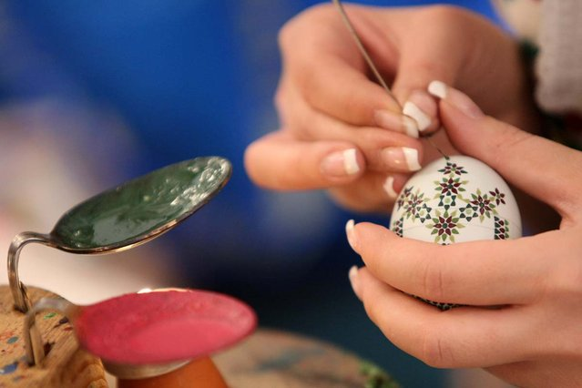 A Sorb egg painter decorates an Easter egg at the annual Easter egg market on March 16, 2013 in Schleife, Germany. Easter is a particularly important time of year for Sorbs, a Slavic minority in eastern Germany, and the period includes the tradition of painting Easter eggs that include visual elements intended to ward off evil. Many Sorbs still speak Sorbian, a language closely related to Polish and Czech.  (Photo by Adam Berry)
