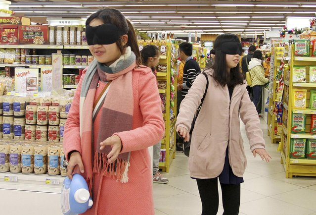 Volunteers attempt to shop blindfolded during an event to mark the International Day of Persons with Disabilities, at a supermarket in Mianyang, Sichuan province December 3, 2014. The event held on Wednesday aimed to raise awareness of blind people and the inconvenience they experienced in lives, local media reported. (Photo by Reuters/Stringer)