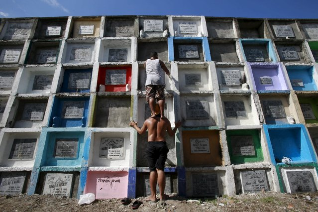 """A man stands on the shoulders of a friend to reach and repaint the tomb of his departed relative buried in an """"apartment-style"""" grave inside a cemetery in Navotas city, north of Manila October 31, 2015. (Photo by Romeo Ranoco/Reuters)"""