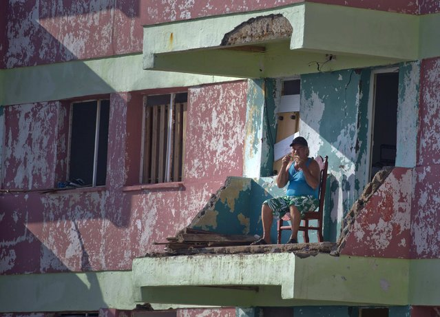 A man eats a piece of chicken while sitting on his balcony that was damaged by Hurricane Matthew, in Baracoa, Cuba, Friday, October 7, 2016. Matthew hit Cuba's lightly populated eastern tip Tuesday night, damaging hundreds of homes in the easternmost city of Baracoa but there were no reports of deaths. Nearly 380,000 people were evacuated and measures were taken to protect infrastructure. (Photo by Ramon Espinosa/AP Photo)