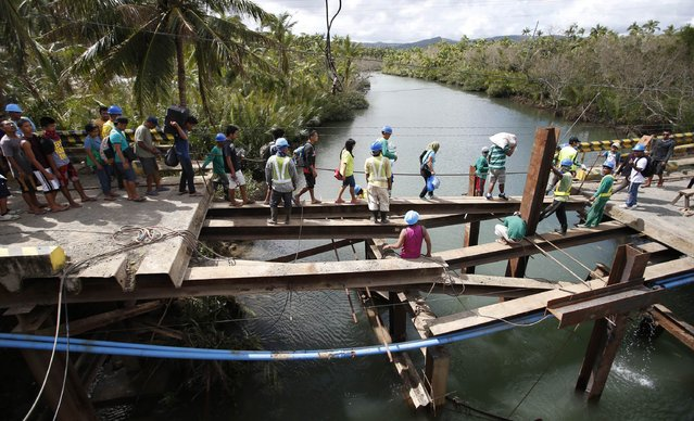 Residents cross a bridge, which was damaged by Typhoon Hagupit, in San Julian, Eastern Samar in central Philippines December 10, 2014. Philippine emergency workers were struggling on Tuesday to reach coastal villages on an island hardest hit by a typhoon where thousands of homes have been wrecked by powerful winds and a storm surge rising three to four meters (10 to 13 feet). (Photo by Erik De Castro/Reuters)