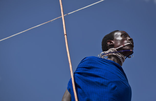 A Maasai warrior catches his swinging necklace with his mouth as he makes the high jump, in which athletes must touch a high line with the top of their heads, at the annual Maasai Olympics in the Sidai Oleng Wildlife Sanctuary near to Mt Kilimanjaro, in southern Kenya Saturday, December 13, 2014. (Photo by Ben Curtis/AP Photo)
