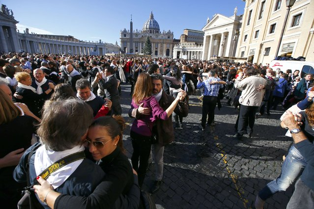 "Couples dance in front of Saint Peter's basilica at the Vatican December 17, 2014. Thousands of people sang ""Happy Birthday"" and danced a mass tango on Wednesday to celebrate the birthday of the first Latin American pope. Argentinian Pope Francis was born in the birthplace of the tango on December 17, 1936. (Photo by Tony Gentile/Reuters)"