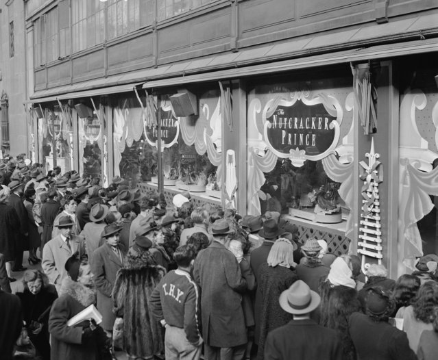 In this December, 24, 1946, file photo, last minute Christmas Eve shoppers gather in front of Macy's window display in New York. A $400 million makeover is giving New York's iconic Macy's store a sleek, new 21st century style. (Photo by Carl Nesensohn/AP Photo)