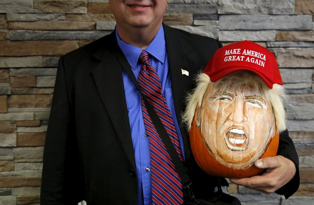 A supporter of U.S. Republican presidential candidate Donald Trump holds a pumpkin painted in the likeness of Trump as he waits to get into a campaign event in Springfield, Illinois, United States, November 9, 2015. (Photo by Jim Young/Reuters)