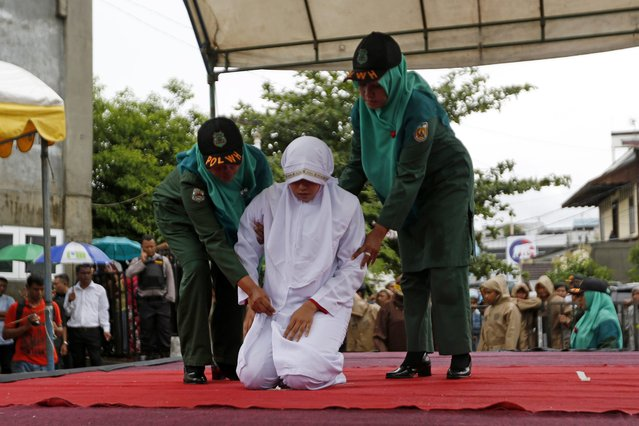 An Acehnese woman is escorted by the sharia police before being whipped in front of the public at Baiturrahman Grand Mosque, Banda Aceh, Indonesia, 17 October 2016. Seven Acehnese couples were sentenced to be whipped 10 to 25 times for violating the sharia law for dating between a man and a woman without married. Aceh is the only province in Indonesia which implemented the Islamic sharia law and whipping punishment is one form of punishment imposed in Aceh for violating the Sharia. (Photo by Hotli Simanjuntak/EPA)