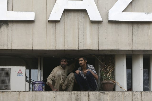 Two men wait to be saved from a burning building in central Lahore May 9, 2013. Fire erupted on the seventh floor of the LDA plaza in Lahore and quickly spread to higher floors leaving many people trapped inside the building. At least three people fell from the high floors trying to avoid the fire that engulfed the building, local media reports. (Photo by Damir Sagolj/Reuters)